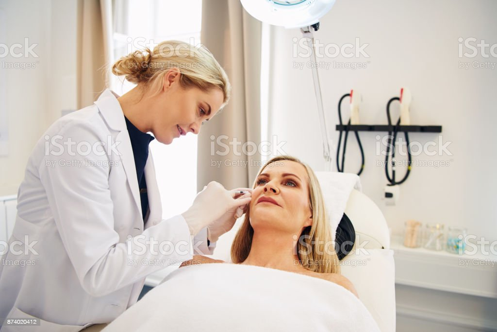 Doctor doing botox injections on a mature client's face royalty-free stock photo