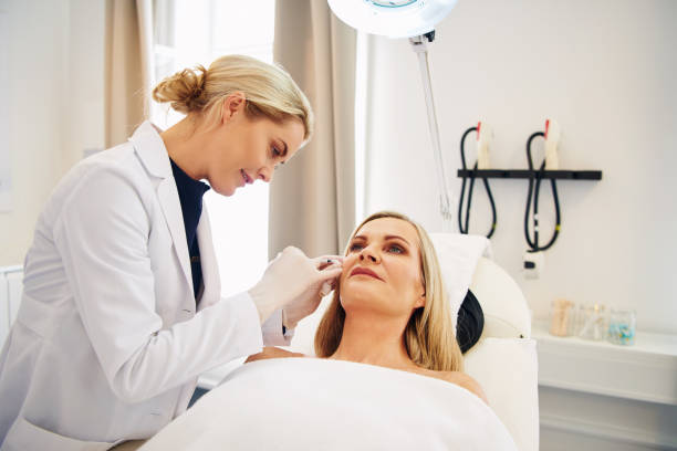 Doctor doing botox injections on a mature client's face stock photo