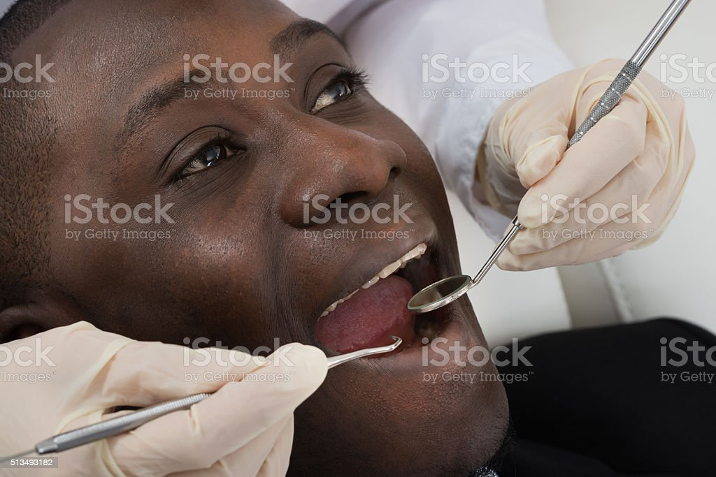 Doctor Doing Dental Check Up Of Patient stock photo