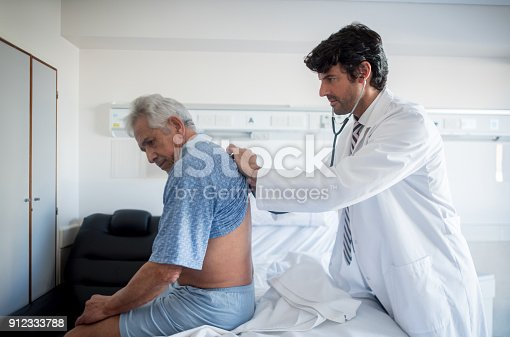 istock Doctor doing his medical rounds at the hospital listening to a patients lungs 912333788