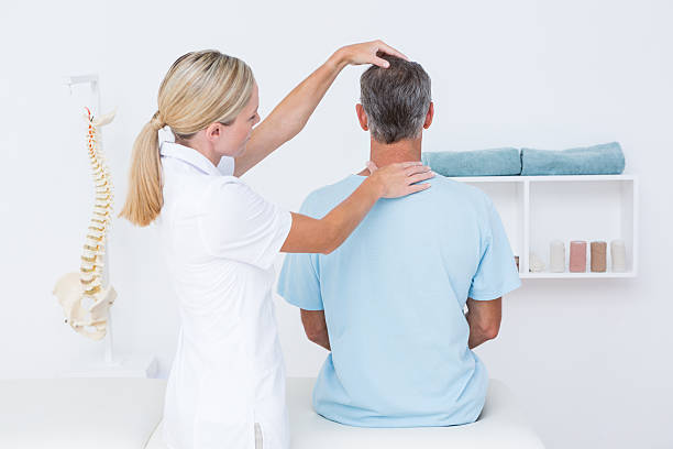 doctor doing neck adjustment - chiropractic care stock photos and pictures