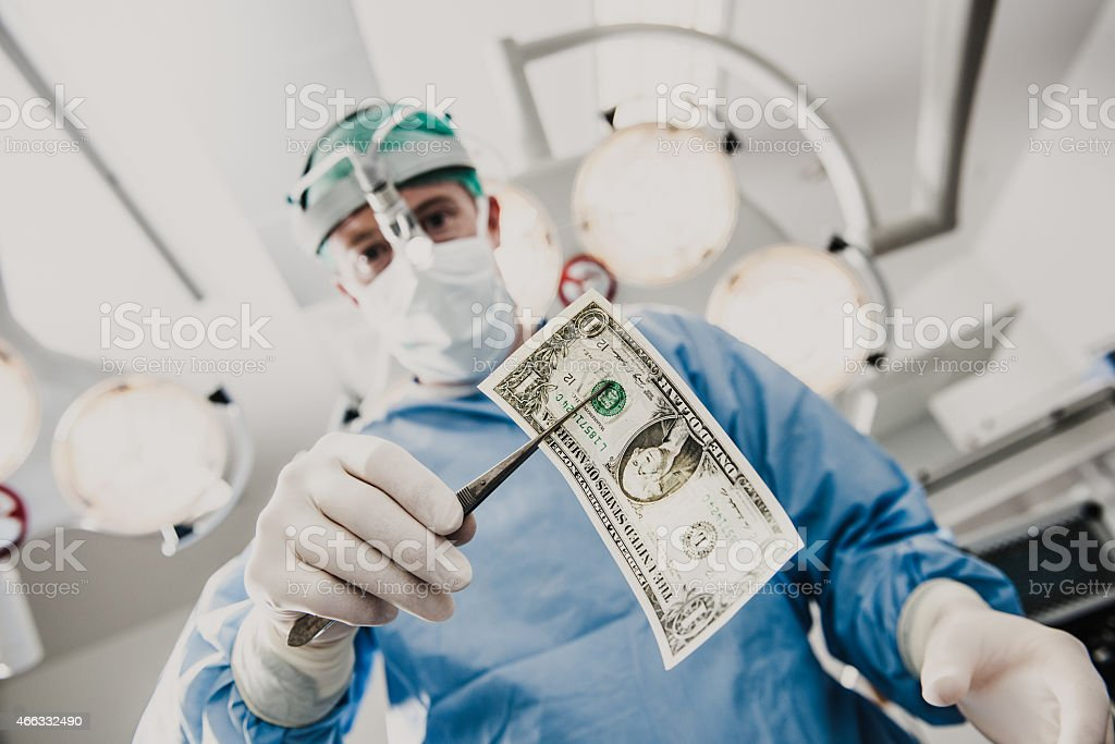 Doctor doing surgery in hospital with money stock photo