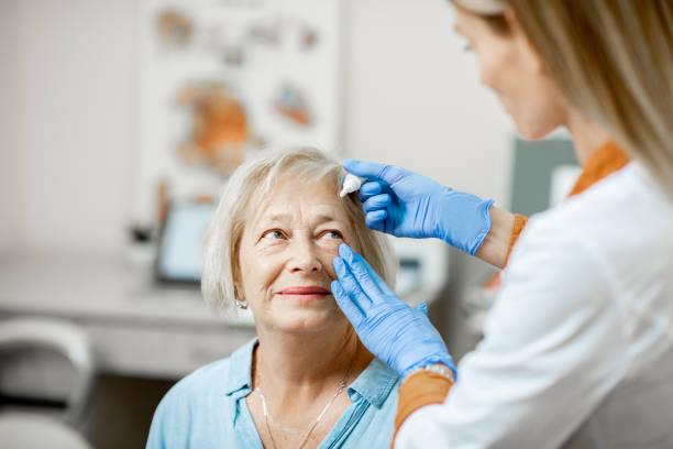 Dokter druipend oog druppels op de ogen van een senior patiënt foto