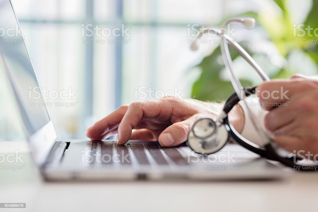 Doctor entering patient notes on laptop in surgery stock photo