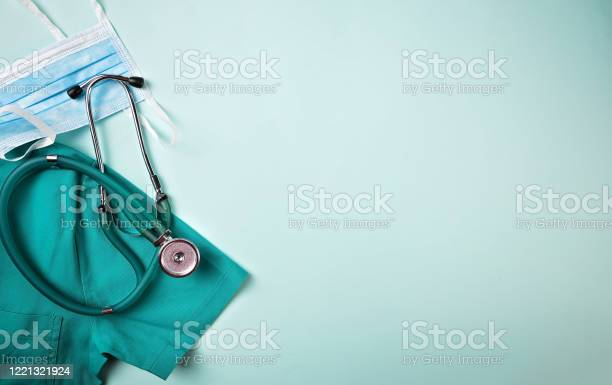Doctor equipment flat lay background Medical flat lay background. COVID 19 healthcare medicine concept. Full frame shot of face mask placed with stethoscope and medical scrubs. All are on green background. Knolling concept. Above Stock Photo
