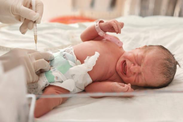 arzt untersucht ein neugeborenes baby - neugeborene krankenhaus outfits stock-fotos und bilder