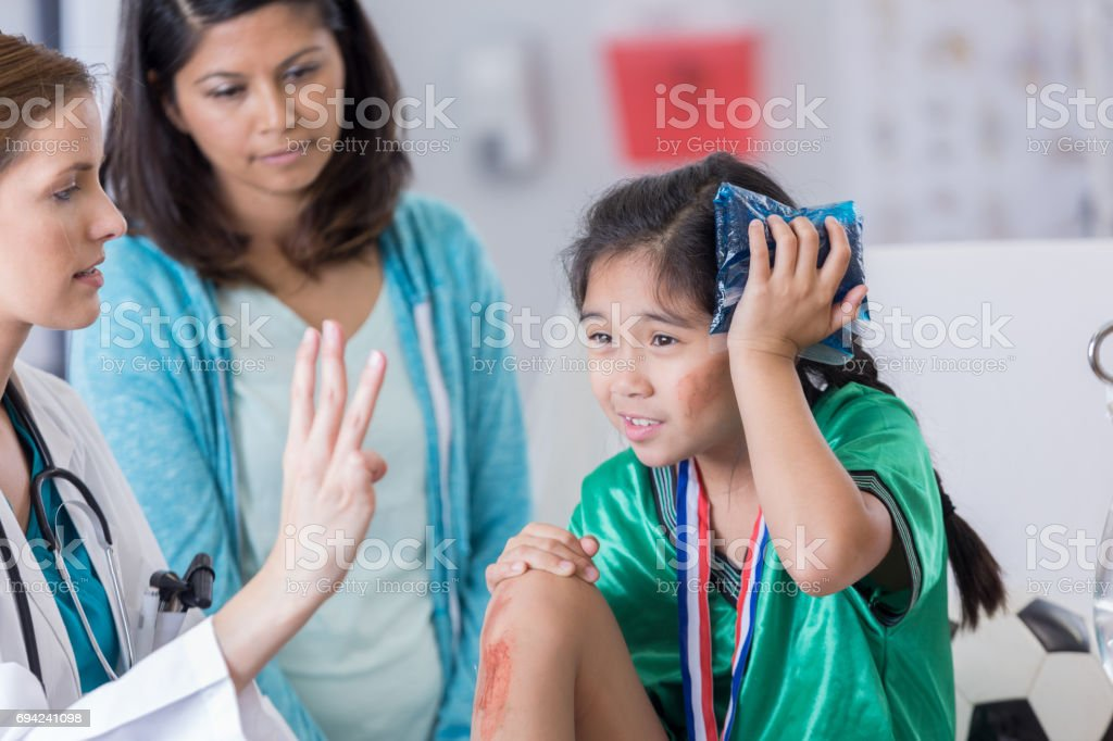 ER doctor examines dazed injured soccer player stock photo