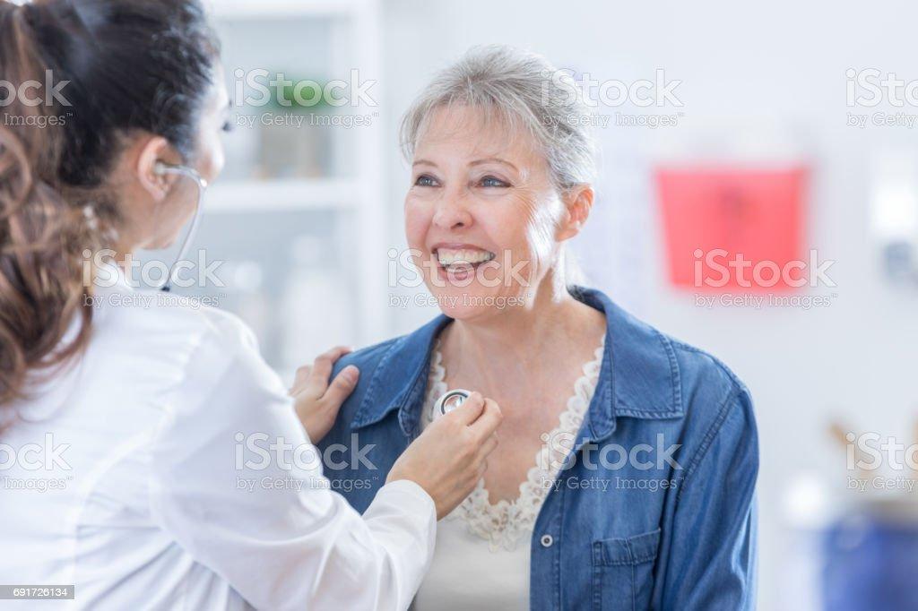 Doctor examines senior woman stock photo