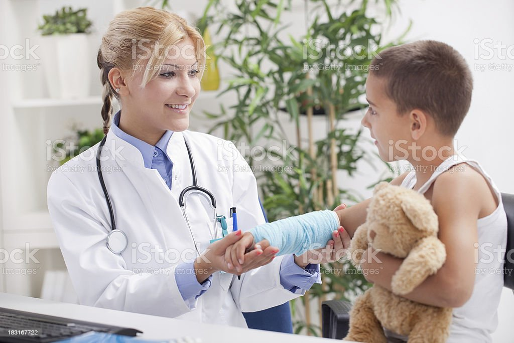 doctor examines, young boy wearing a blue cast stock photo