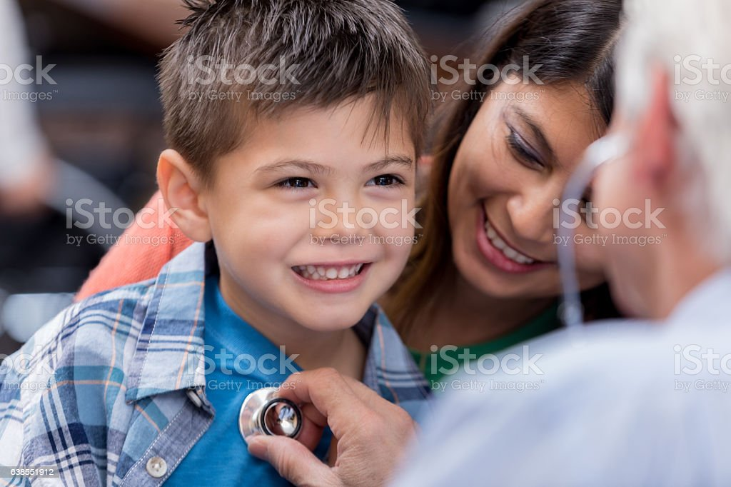 Doctor examines young patient during well check stock photo