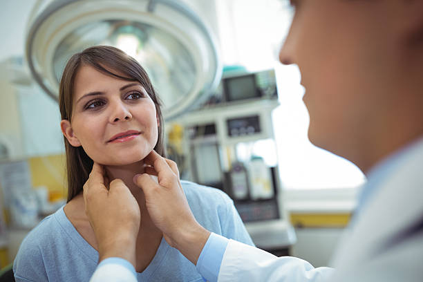 Doctor examining a female patients neck Doctor examining a female patients neck in the hospital human gland stock pictures, royalty-free photos & images