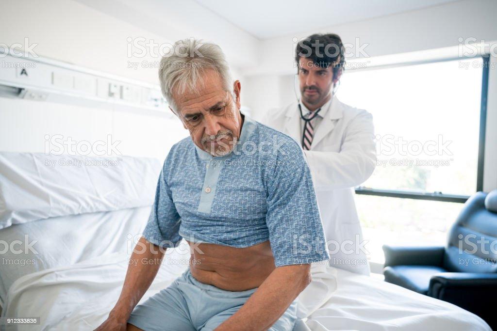 Arzt in einem Krankenhaus senior Patienten überprüft seine Lungen – Foto