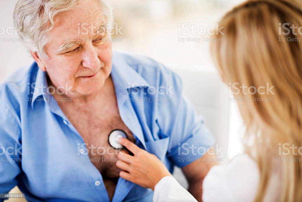 Doctor examining a senior patient. stock photo