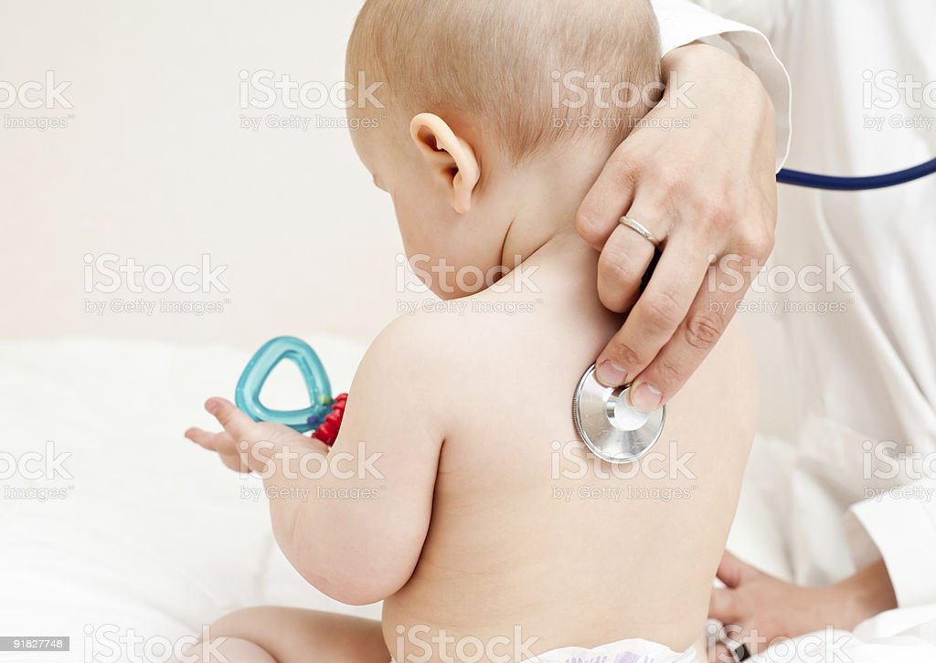 Doctor examining a toddler's lungs stock photo