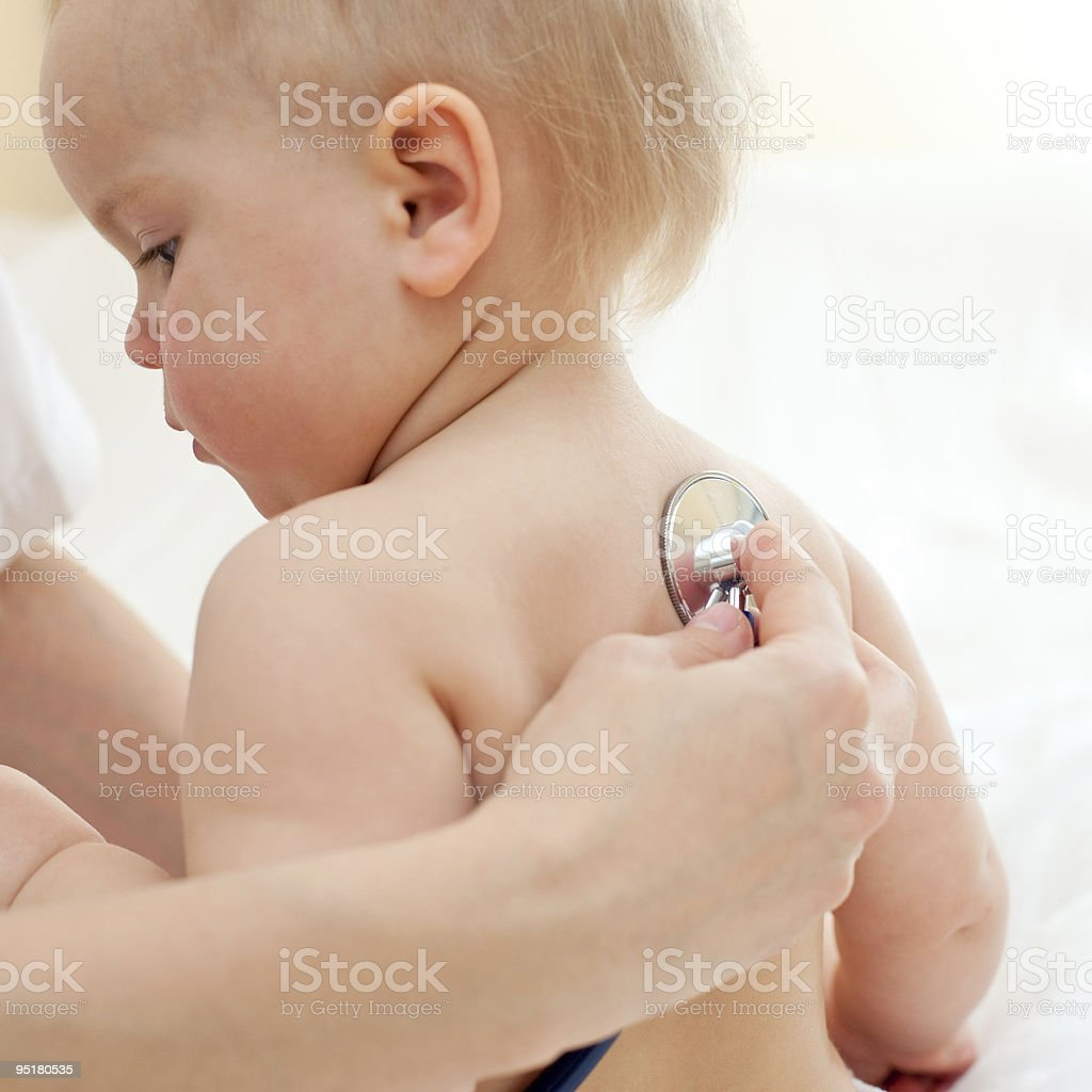 A doctor examining a young baby's back royalty-free stock photo