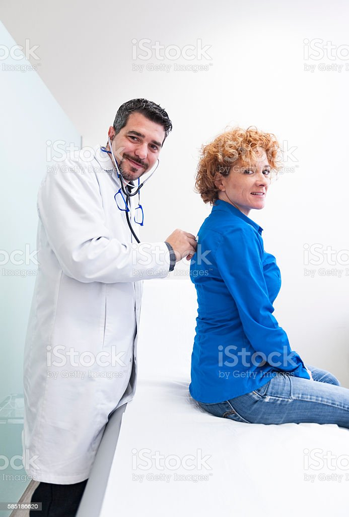 Doctor examining a young woman stock photo