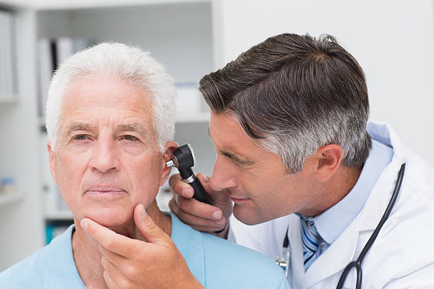 Doctor examining an elderly patient's ear with an otoscope Male doctor examining senior patients ear with otoscope in clinic human ear stock pictures, royalty-free photos & images