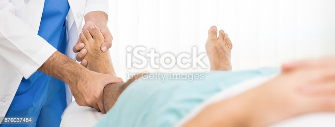 867056016istockphoto Doctor examining and treating broken leg patient on the bed in hospita 876037484