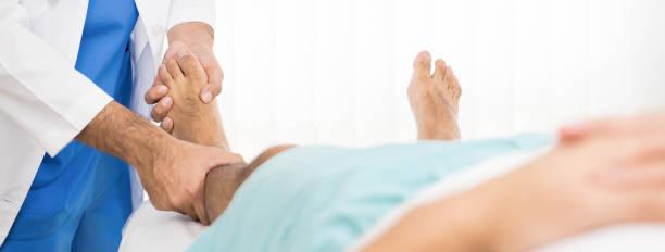 doutor examinando e tratando o paciente de perna quebrada na cama no hospita - ortopedia - fotografias e filmes do acervo