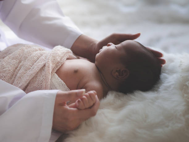 Doctor examinando al recién nacido asiático acostado en la cama en la clínica. Concepto de salud del bebé - foto de stock