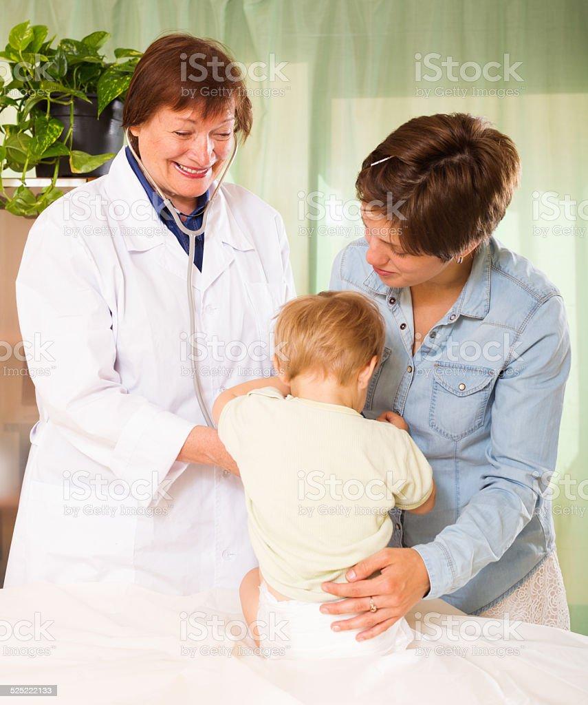 doctor examining baby at clinic office stock photo