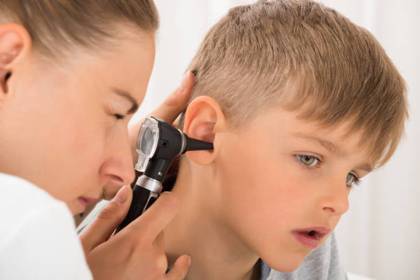 doctor examining boy's ear - infectious disease stock pictures, royalty-free photos & images