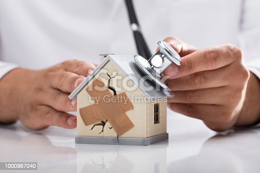 Doctor's hand examining broken house with stethoscope on reflective desk