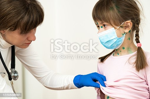 857285148 istock photo Doctor examining child girl covered with green rashes on face and stomach ill with chickenpox, measles or rubella virus. 1220538551