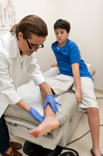 Doctor examinar niño de la pierna - foto de stock
