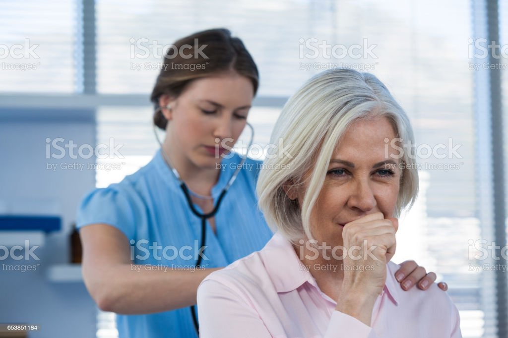 Doctor examining coughing patient stock photo