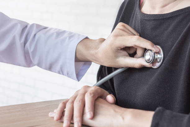 doctor  examining female patient heart beat at a hospital stock photo
