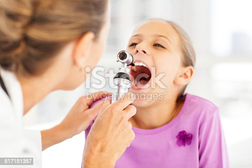 istock Doctor Examining Girl's Throat With Otoscope In Clinic 517151357
