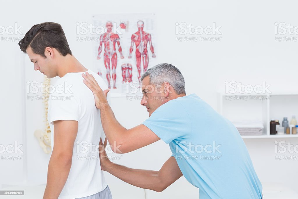 Doctor examining his patient back stock photo