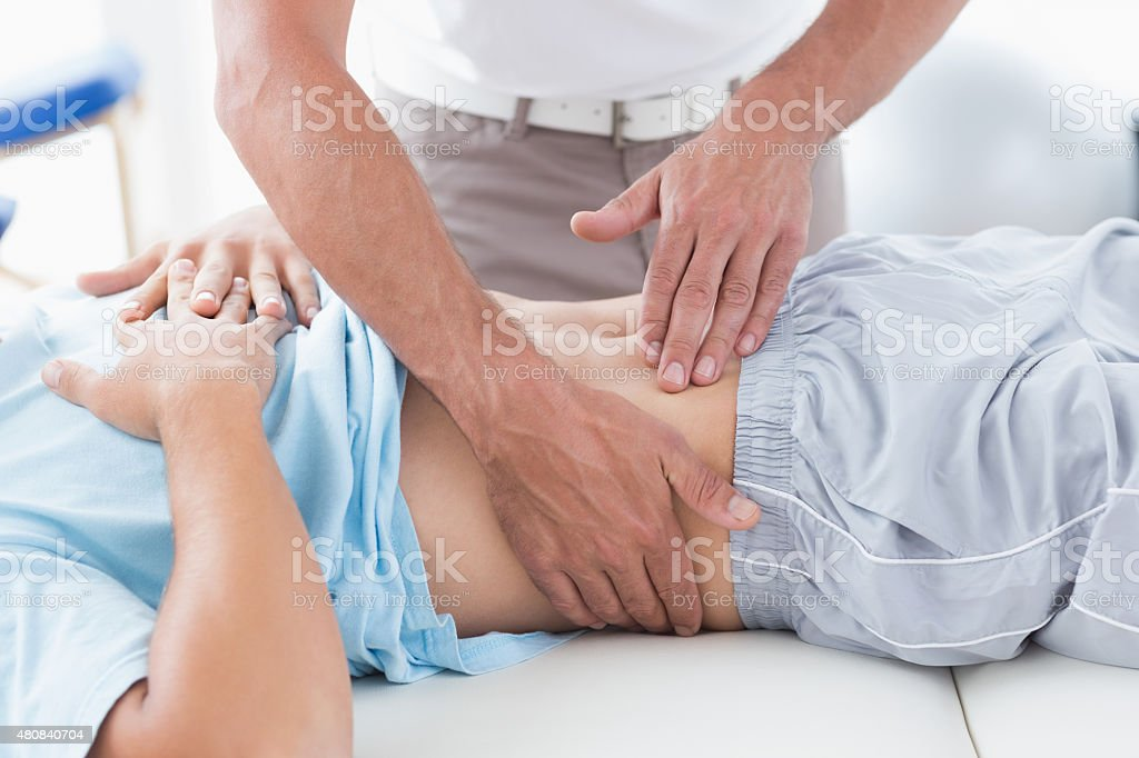 Doctor examining his patient stomach stock photo
