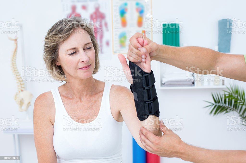 Doctor examining his patients wrist stock photo