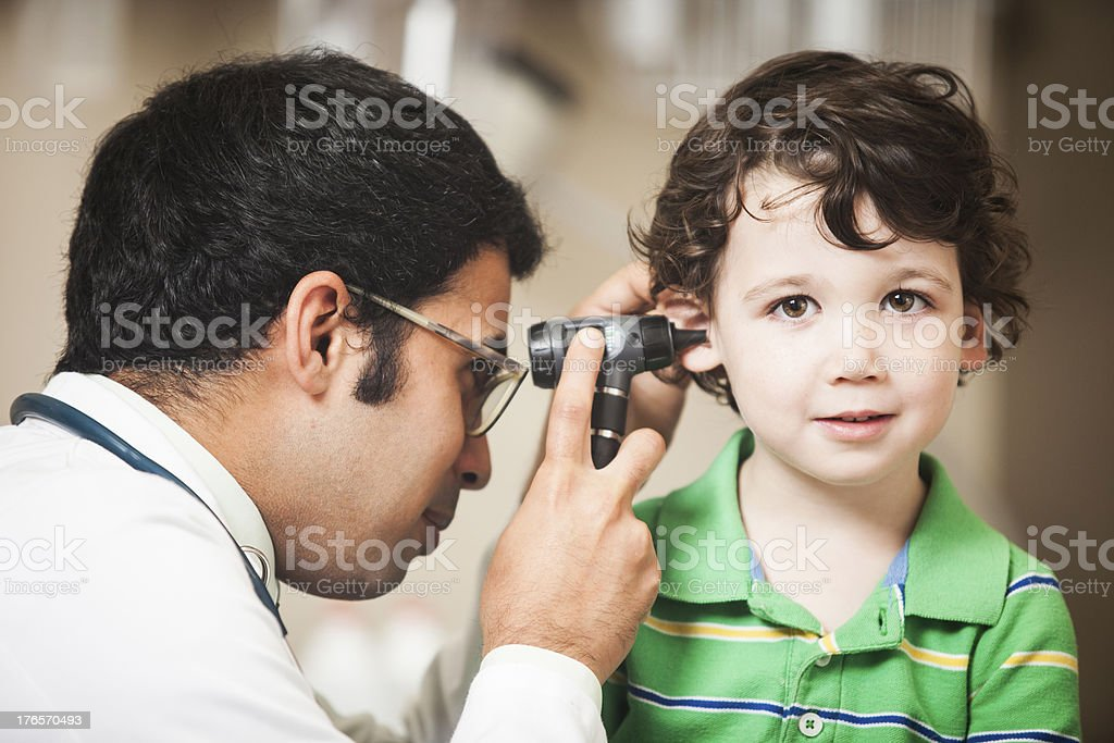 Doctor Examining Little Boys Ear stock photo