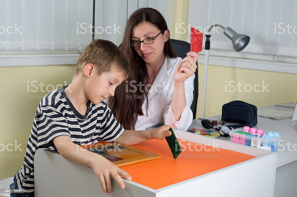 Doctor Examining Little Boy's Logical Thinking With Colored Geometric Shapes stock photo