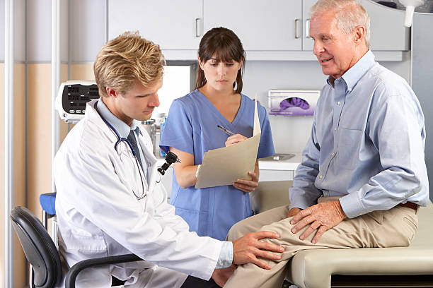 Doctor Examining Male Patient With Knee Pain stock photo