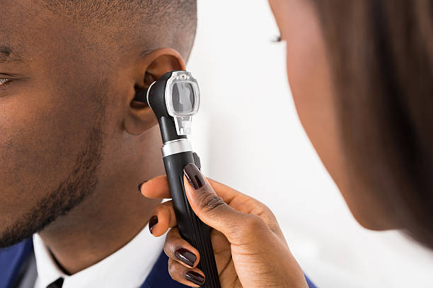 Doctor Examining Male Patient's Ears stock photo