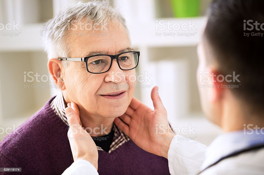 Doctor examining old patient lymph glands stock photo