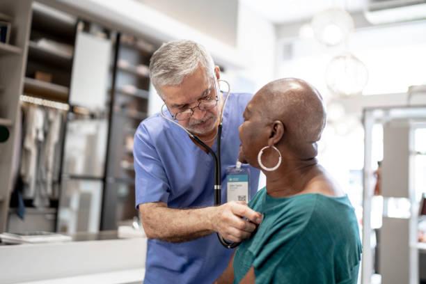 doctor examining patient at home - pensionati lavoratori foto e immagini stock