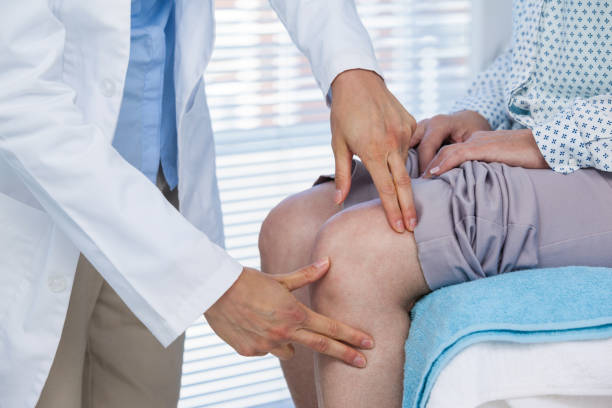 doctor examining patient knee - pain stock photos and pictures