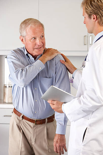doctor examining patient with shoulder pain - shoulder surgery stock photos and pictures