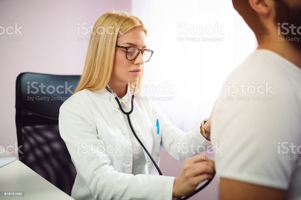 Doctor examining patient with stethoscope in medical office. Doctor using stethoscope to exam man patient heart. Portrait of female doctor examines a patient with stethoscope. stock photo