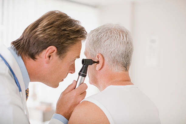 doctor examining patients ear in doctors office - ear stock photos and pictures