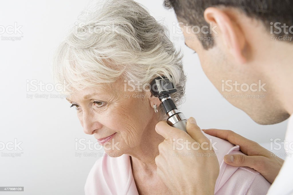 Doctor Examining Patient's Ear Using Otoscope In Clinic stock photo