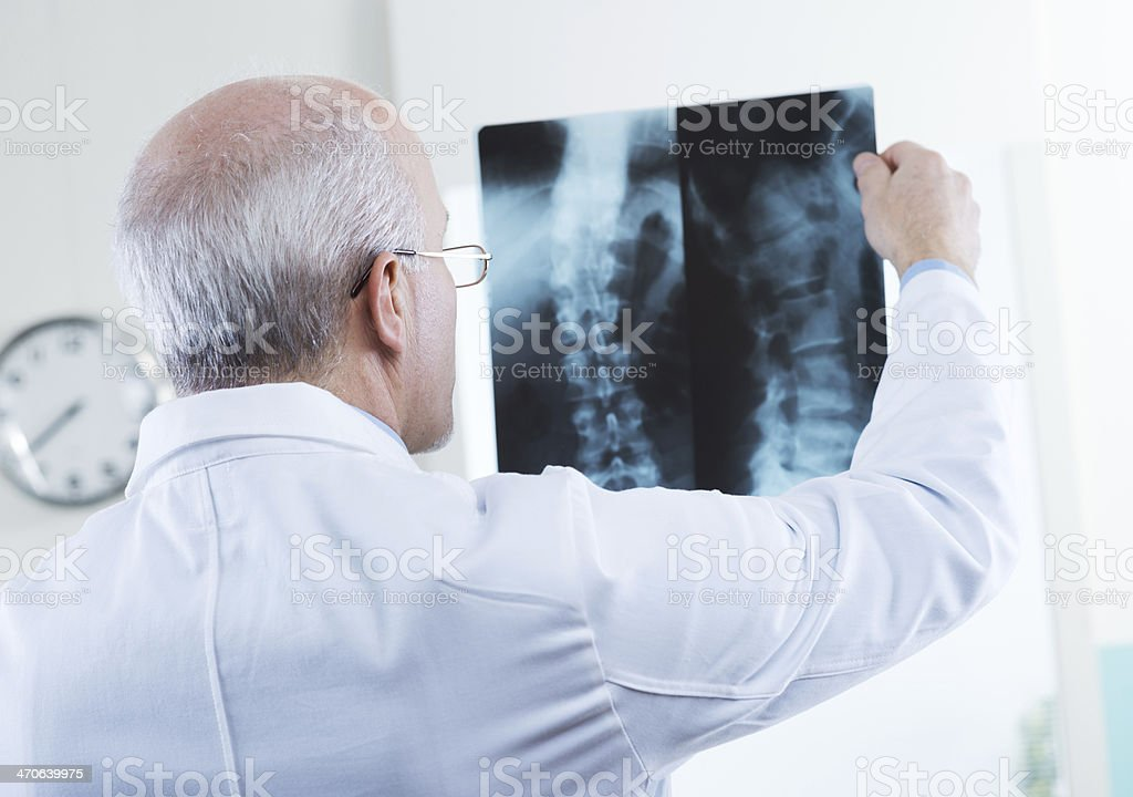 Doctor examining patient's spinal X-Rays stock photo