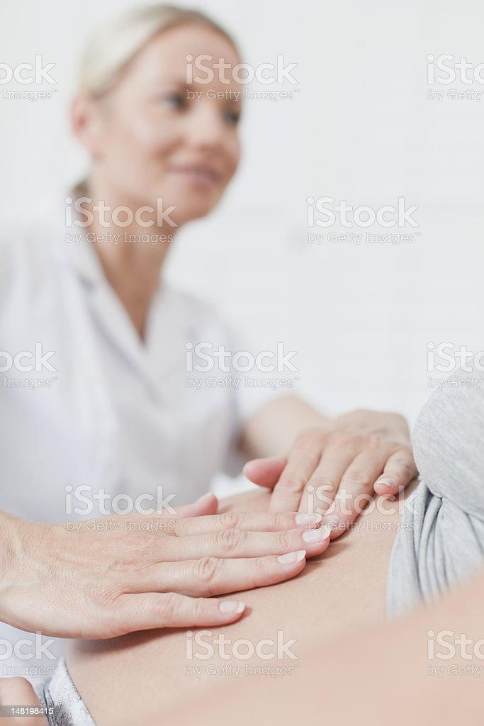 Doctor examining pregnant womans belly stock photo