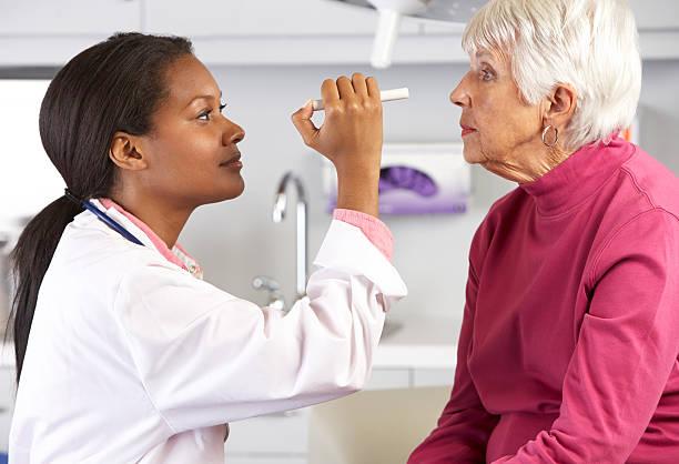 Doctor Examining Senior Female Patient's Eyes stock photo