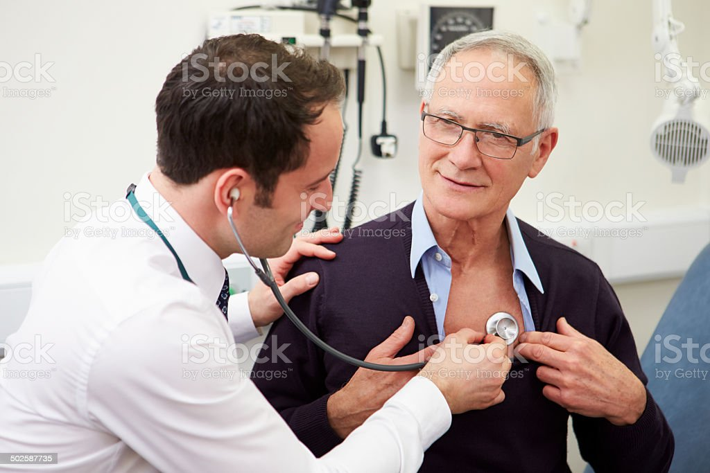 Doctor Examining Senior Male Patient In Hospital stock photo